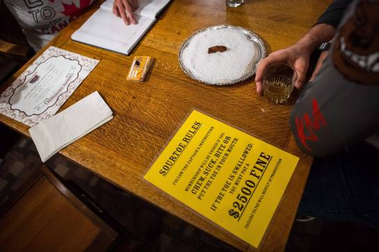A patron waits to drink the Sourtoe Cocktail, a shot of whisky containing a dehydrated human toe, as the rules are displayed on the table, in Dawson City, Yukon, in a July 1, 2018, file photo.