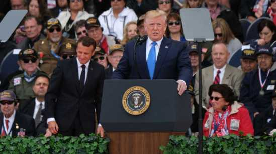 U.S. President Donald Trump speaks as French President Emmanuel Macron (C-L)and American Battle of Normandy veterans and family members look on at the main ceremony to mark the 75th anniversary of the World War II Allied D-Day invasion of Normandy.